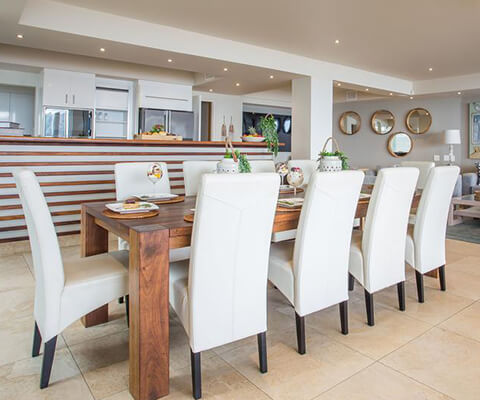 Overview of a dining room with white chairs