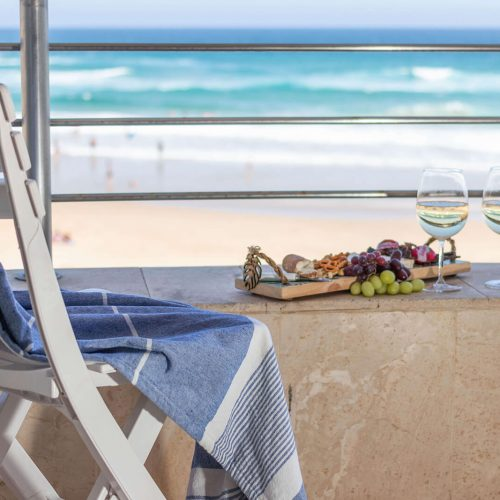 Close-up of a chair with snacks and wine on a patio overlooking the ocean